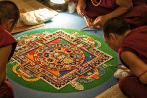 Monaci tibetani durante la preparazione di un mandala. (Foto da savetibet.ru).