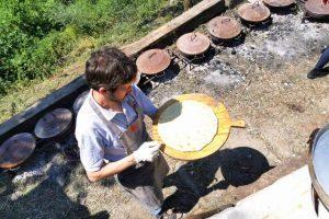 Preparazione della pizza che sarà cotta con i tradizionali 'testi' di ghisa.